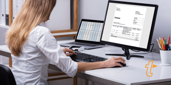 A woman sat at a desk creating an invoice