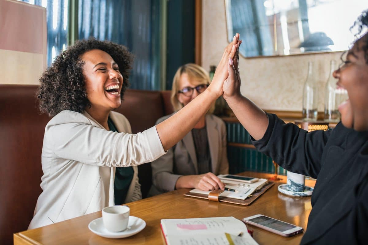 women high-fiving in a business setting