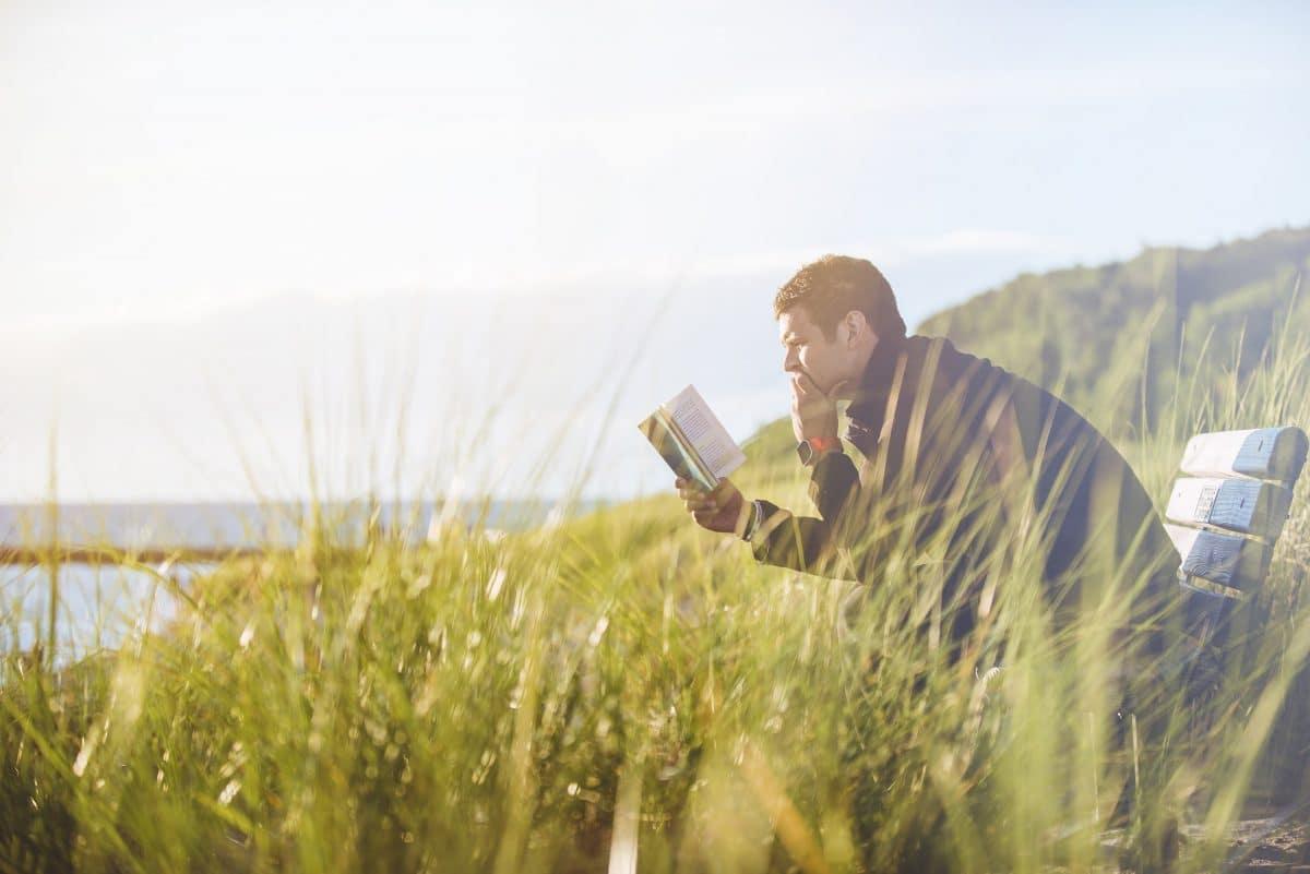 man sitting on bench reading