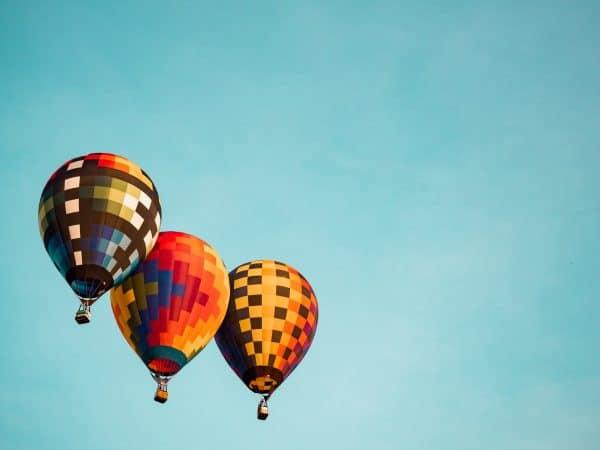 three hot hair balloons against a blue sky