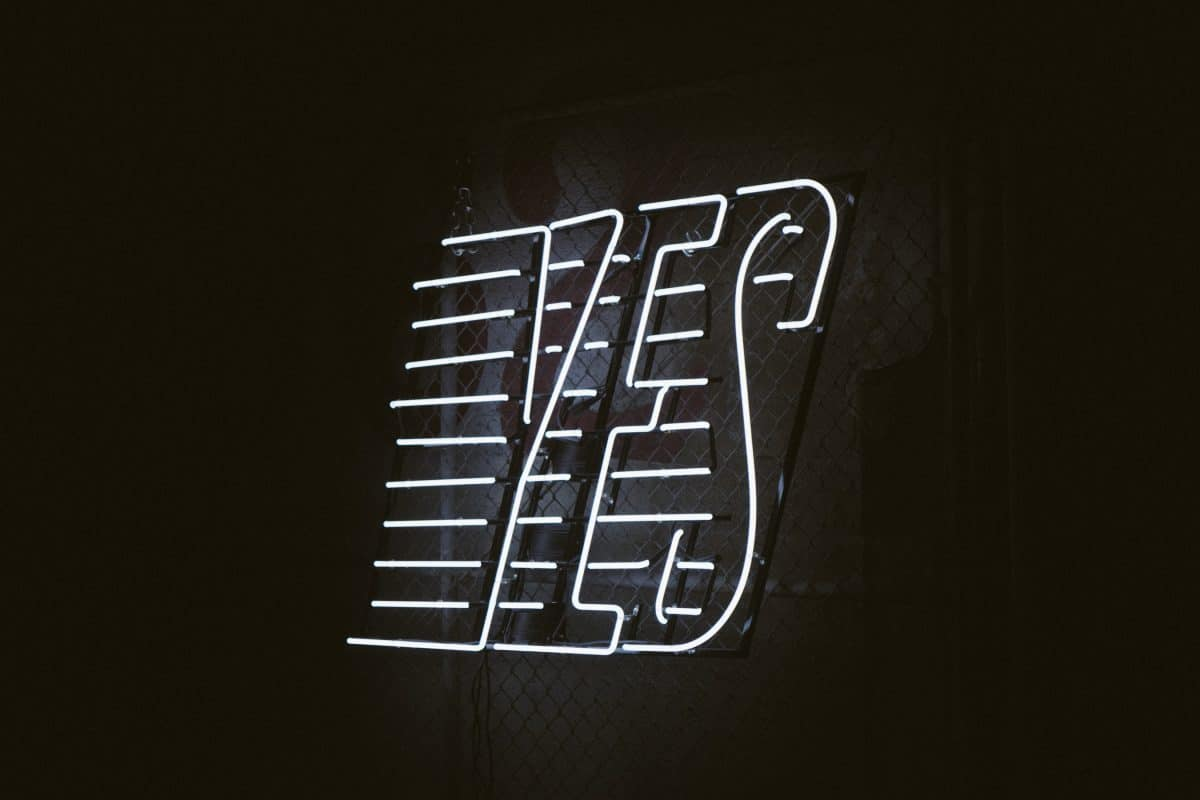 a white neon sign that reads 'yes'