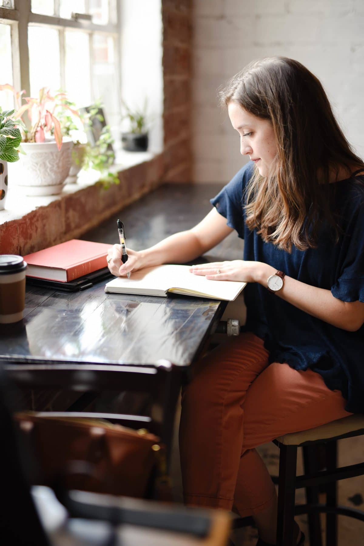 woman sitting at a desk writing in a notebook