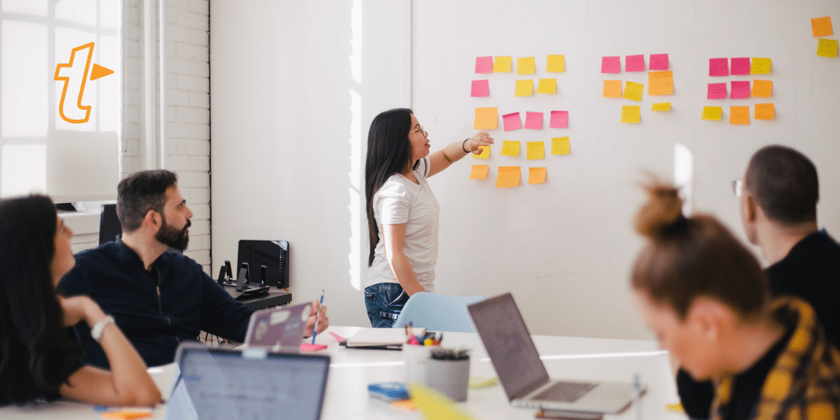 woman placing sticky notes on whiteboard