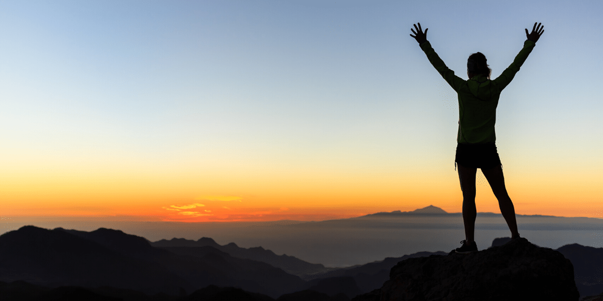 man with arms up on top on mountain