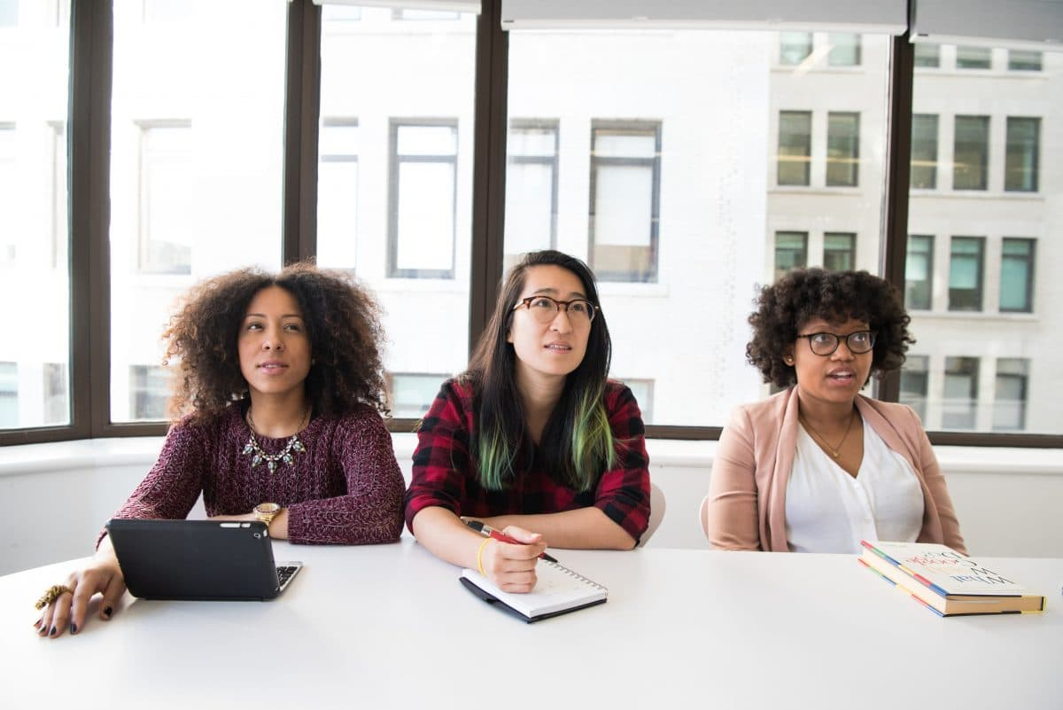 A black woman, an Asian woman, and another black woman sit behind a desk.