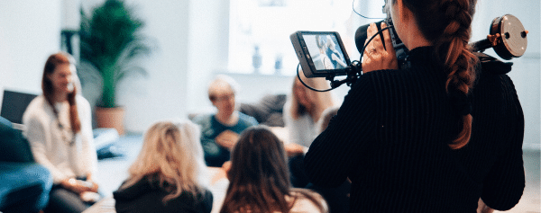 Woman uses camera to record team in a meeting.