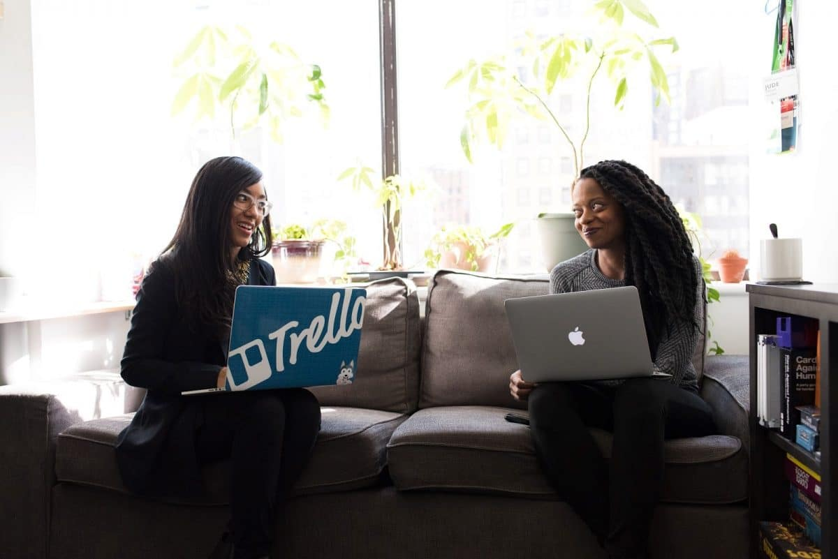 Two women sitting next to each other with laptops smile, illustrating recruitment idea 9.