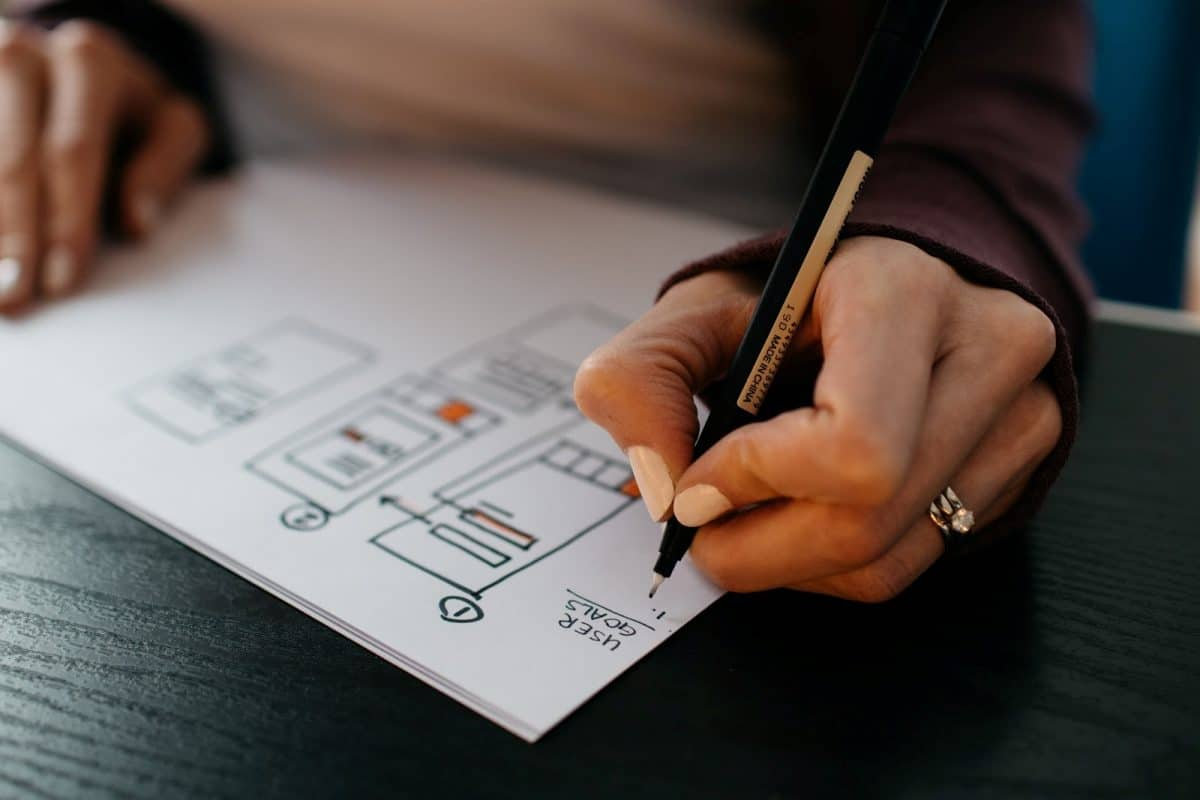 Woman draws user flow on a piece of paper. She is applying recruitment idea 3: improve the application experience.
