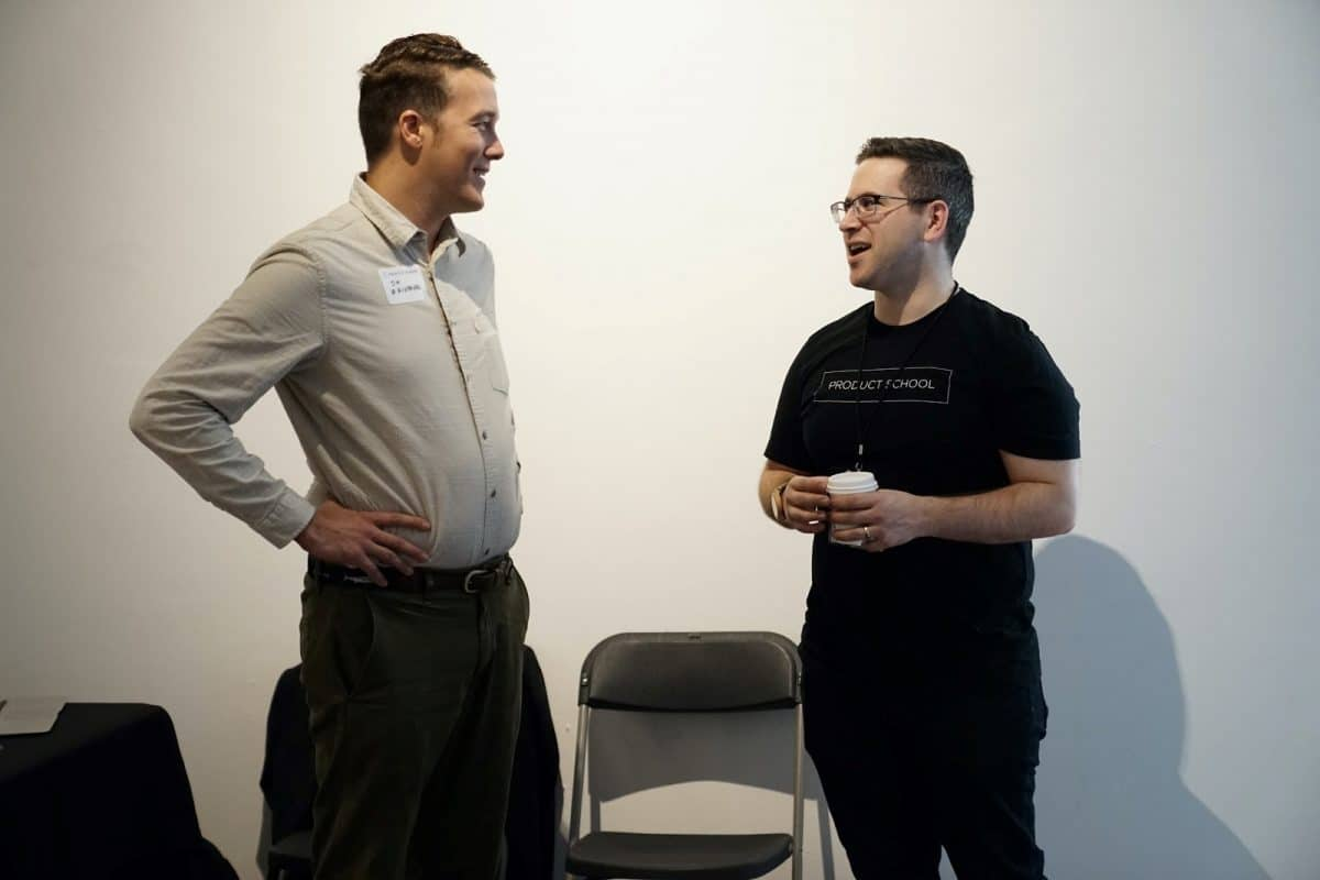 Two men stand chatting in a networking event, illustrating the importance of recruitment idea 6, referrals.