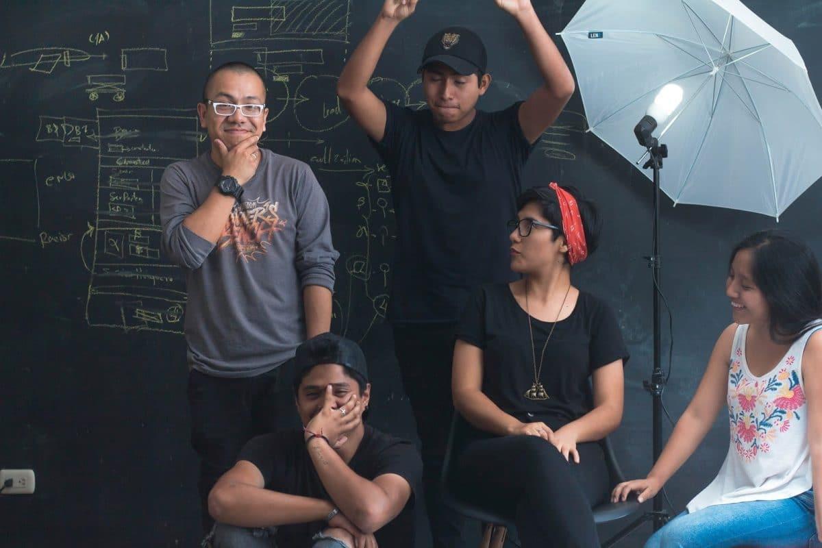 Five team members in improvised film set to illustrate recruitment idea 7, make a recruiting video.