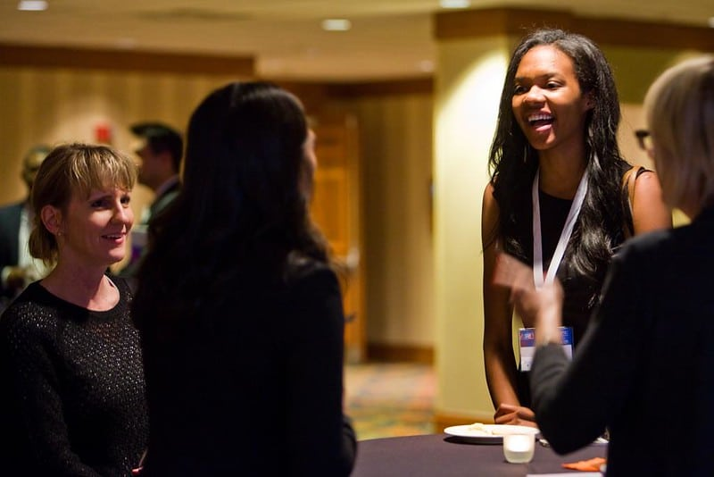 Women of different races and ethnicities chat at a work event.