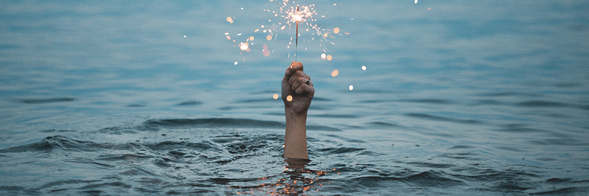 Hand holding sparkler in the water