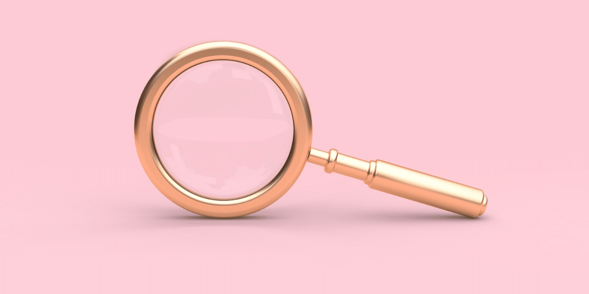 A magnifying glass on a pink background