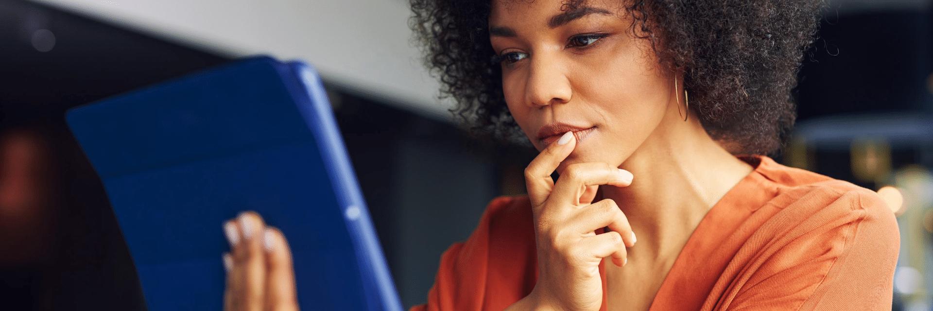 woman in an orange top looking at screen