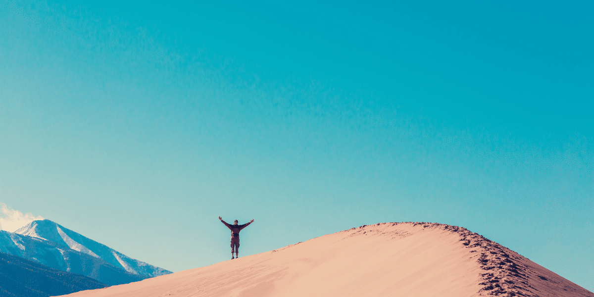 person on top of mountain with arms raised