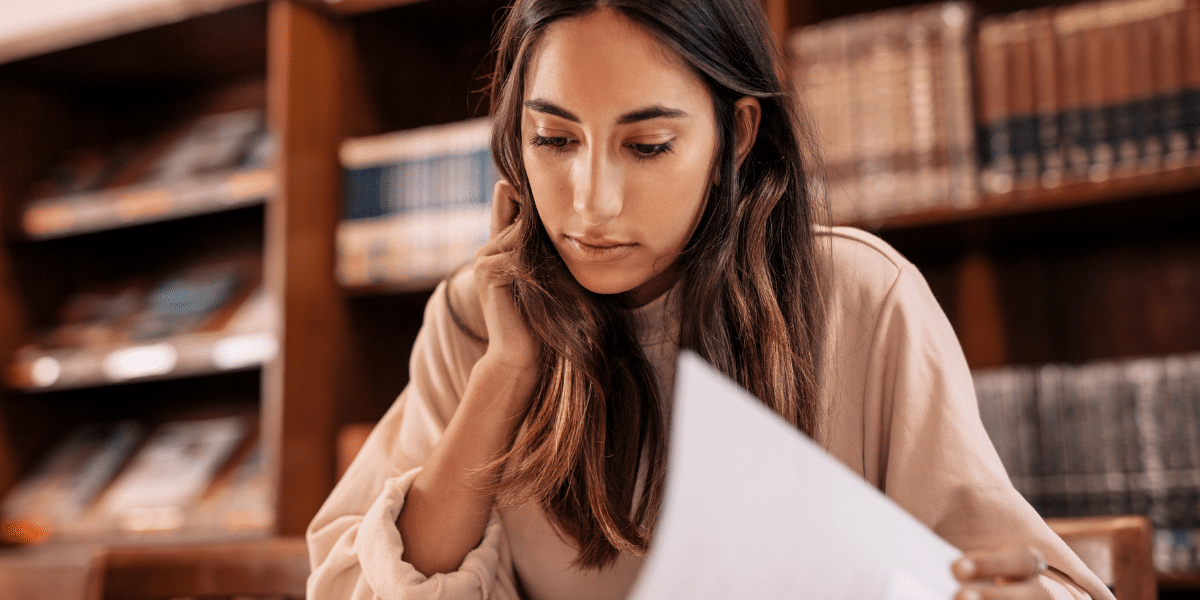 female reading a document in a library