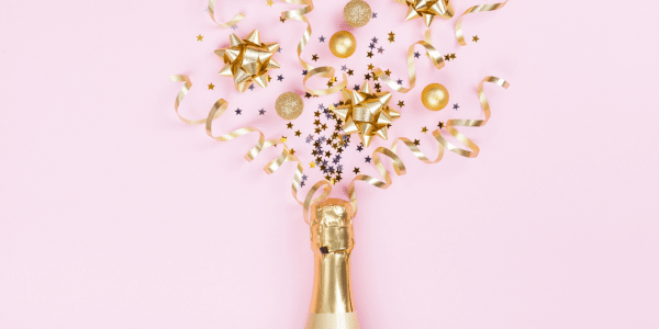 champagne with confetti popping out on pink background