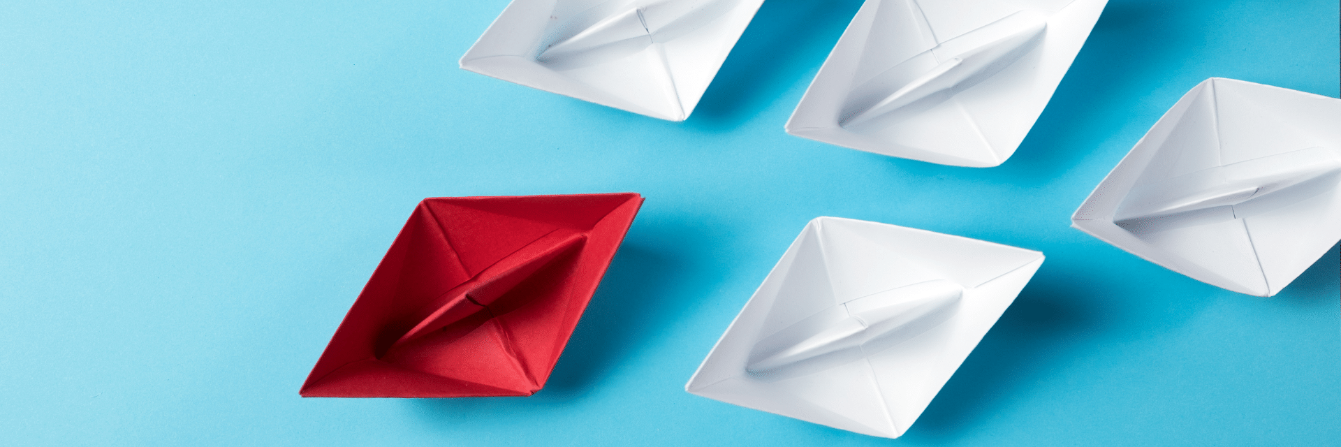 red paper boat leading white paper boats