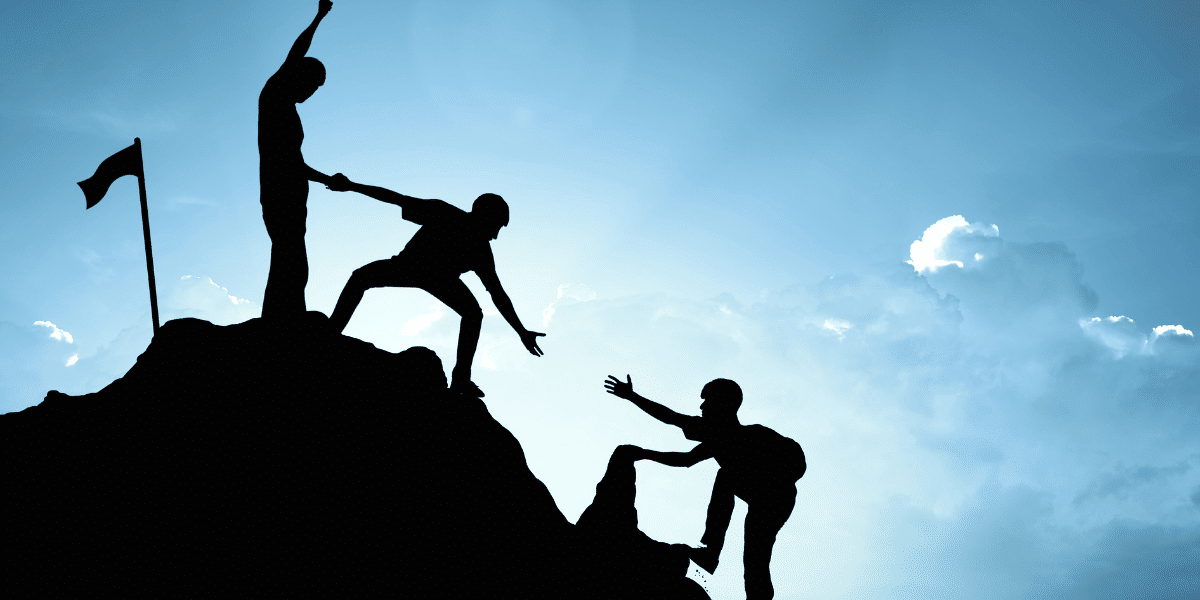 mountaineers helping each other to summit