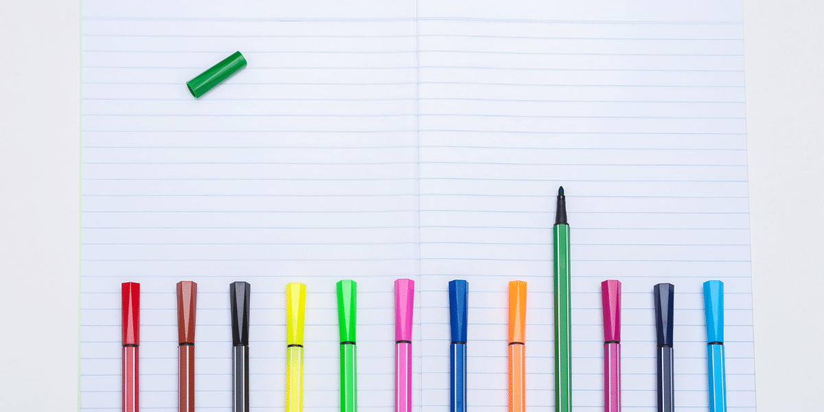 colorful pens on lined notebooks