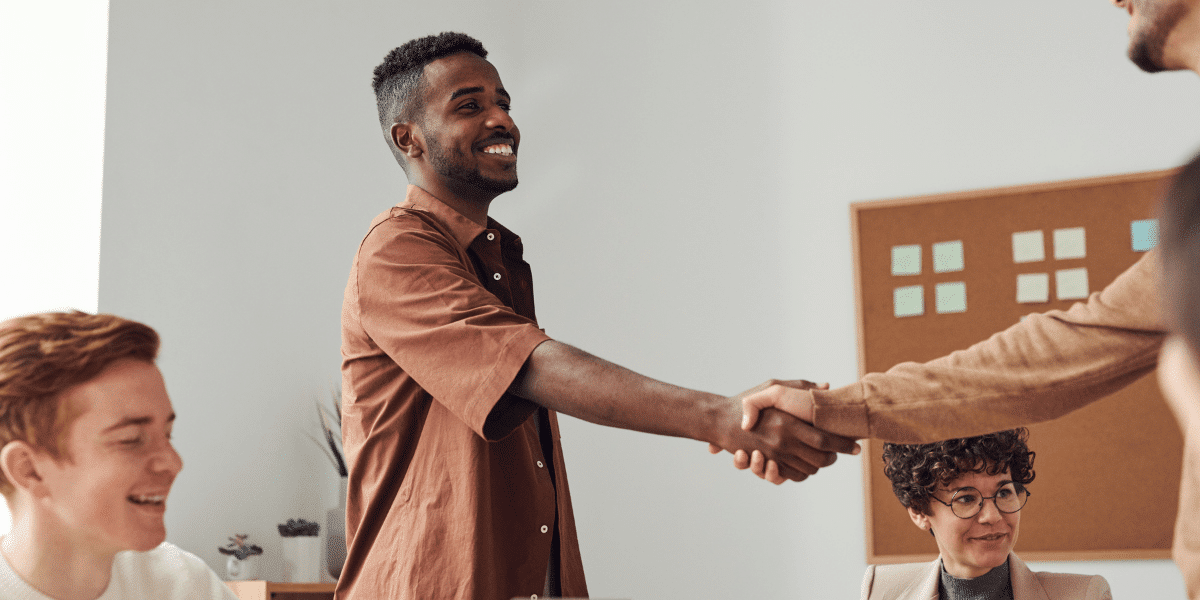 two people shaking hands over desk