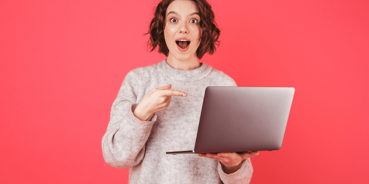 woman pointing at laptop and smiling