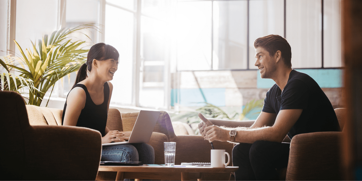 two people chatting and smiling on sofas