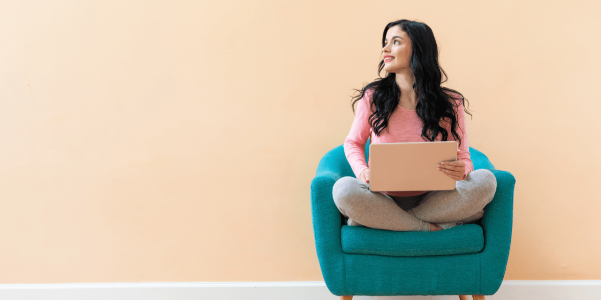 woman sat on sofa with laptop