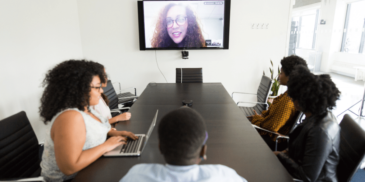 Several people in a conference room, all facing the screen which has a woman smiling and talking on.