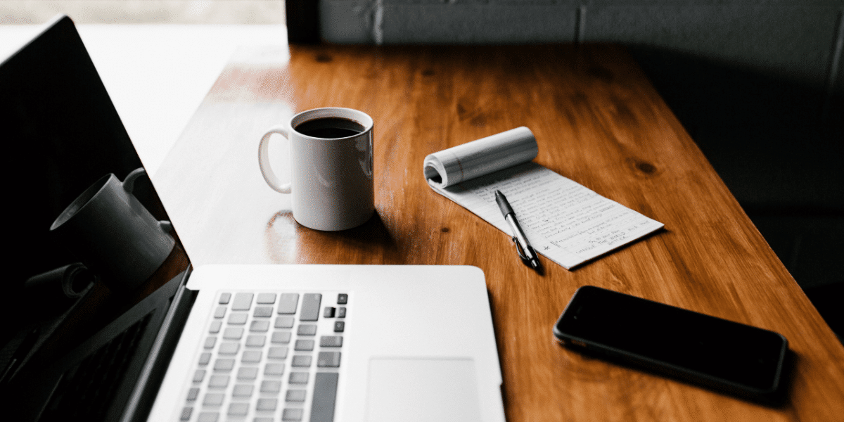 Pen and paper with a list on, next to a laptop, phone and coffee cup