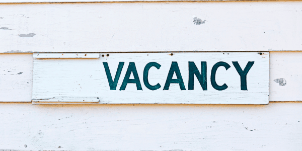 Bright VACANCY sign on a slatted wooden background