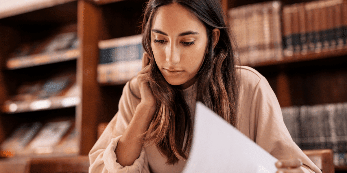 A woman in a library, reading a book and doing research