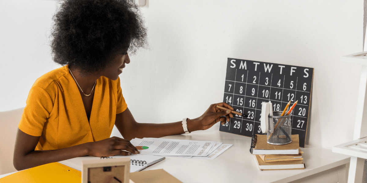 A woman checking a desk calendar and making notes