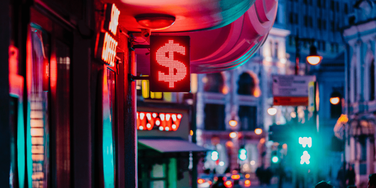 A neon street sign with the dollar sign