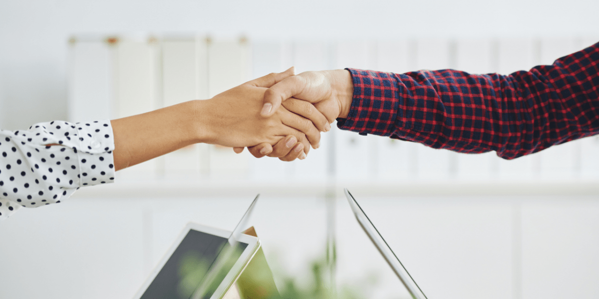 Two people shaking hands, with only their arms & hands in view.