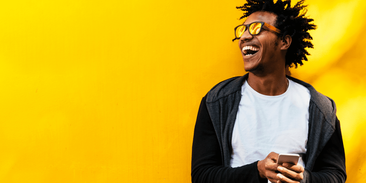 A man with sunglasses on laughing and holding his phone against a bright yellow wall