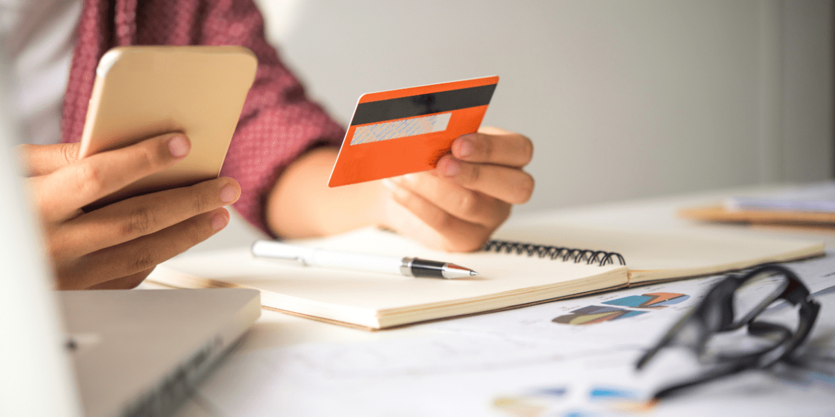 A person making a payment on their phone, holding up their credit card. They're on a busy working desk with a notebook, laptop and glasses.