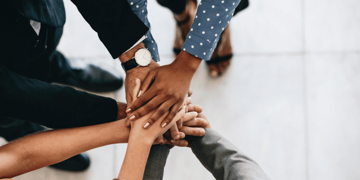 3 people with their hands put into the middle, in a circle, suggesting teamwork