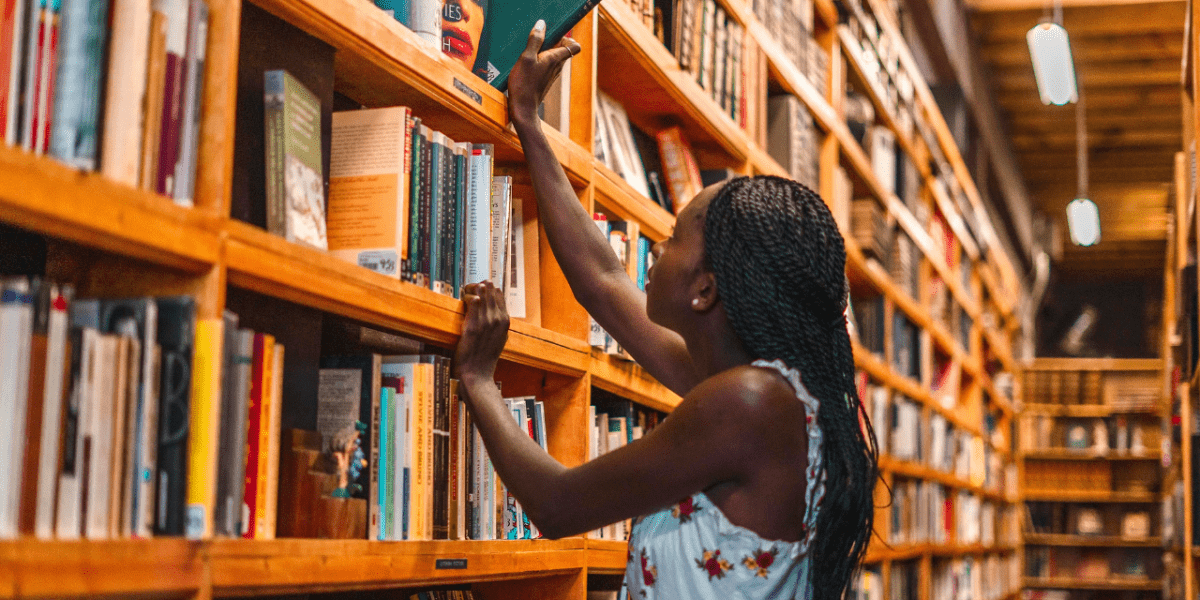 A woman pulling out a book from a high shelf in a library