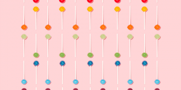 Multicoloured lollipops laid out neatly in lines on a bright pink background.