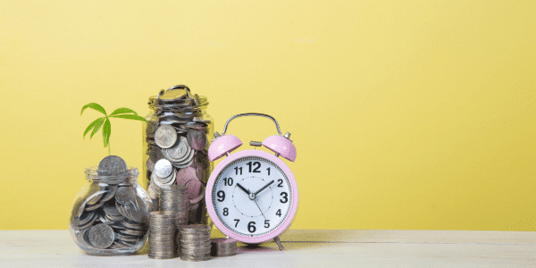 A pink clock next to a jar of change, on a bright yellow background