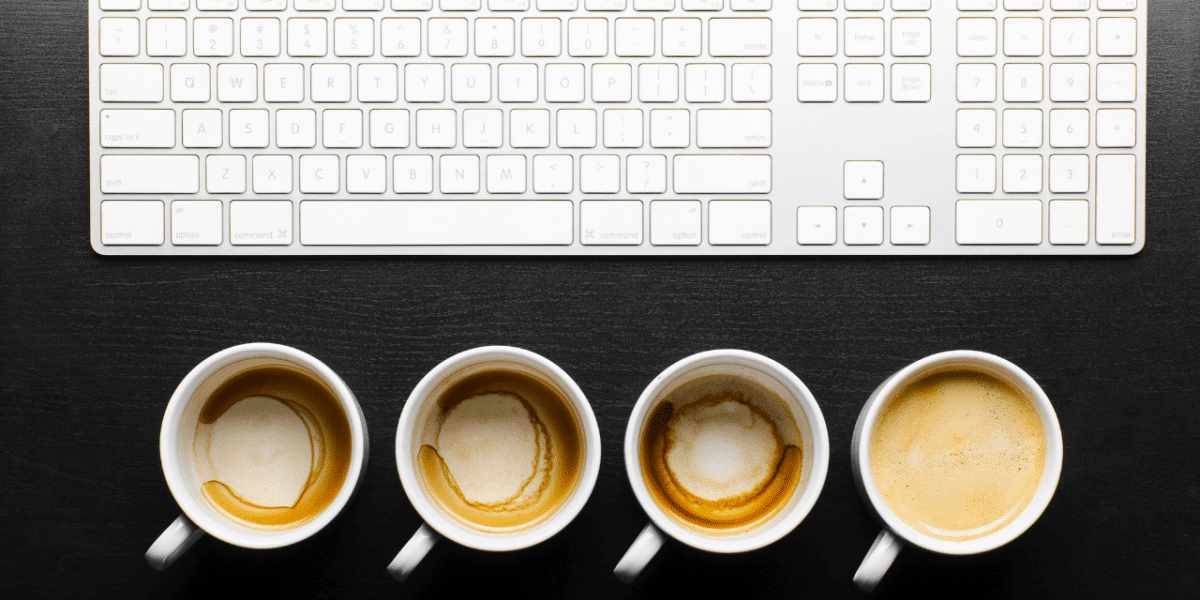 The image shows a keyboard pushed back on a desk, with 4 coffee cups lined up in front of it. 3 are empty and one is full