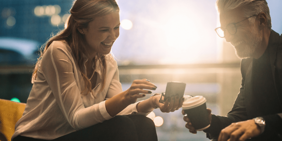 A man and woman laughing and chatting with cups of coffee in a professional setting