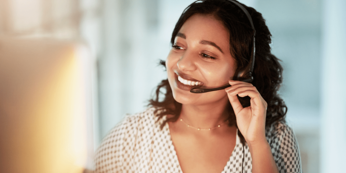 A telesales employee on the phone, using a headset. She is smiling during her conversation with the customer.