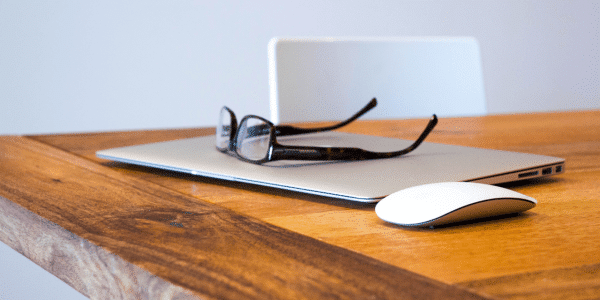 A closed laptop, with a pair of glasses laid on top, indicating work is finished for the day!
