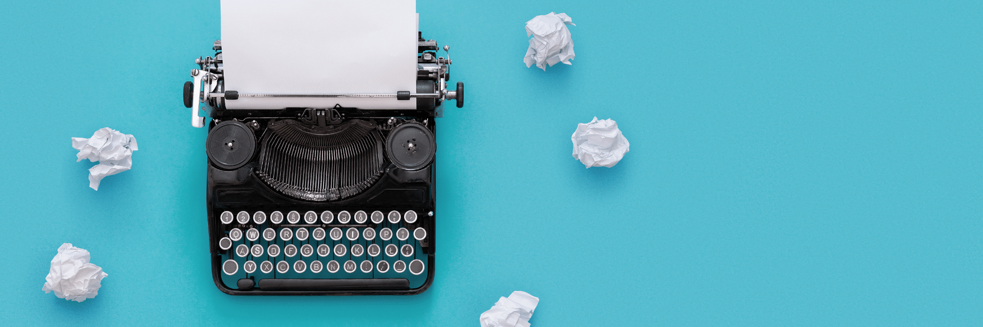 typewriter on a blue background with scrunched up paper surrounding