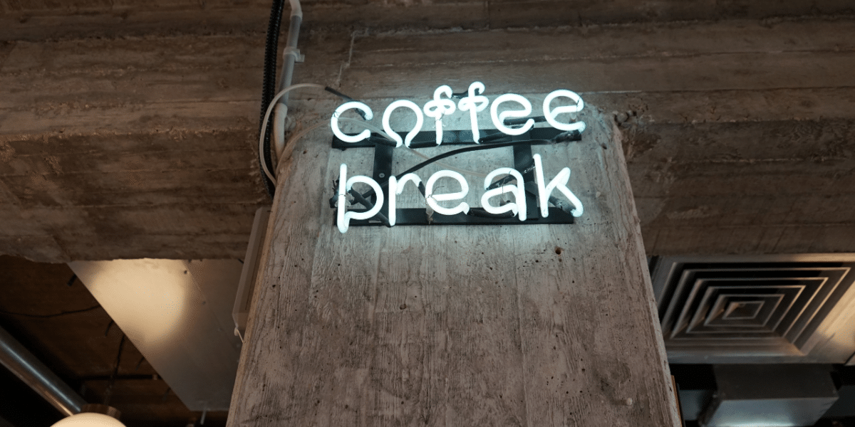 A blue-ish white neon sign against an industrial wall reading 'COFFEE BREAK'