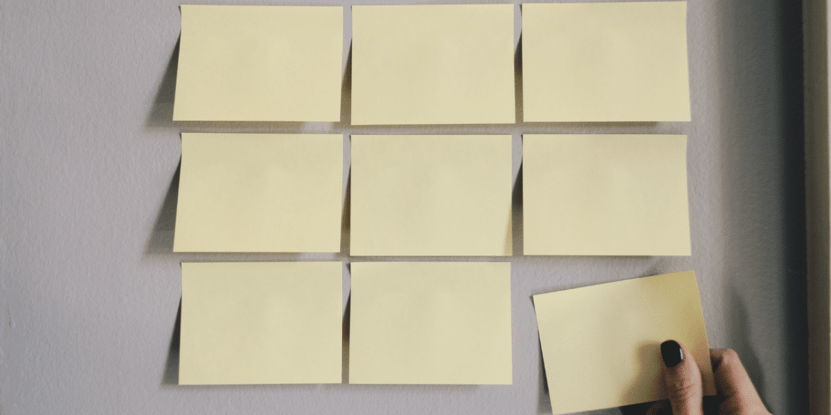 Yellow post-it notes lined up on a wall. A hand is in the process of putting another one up