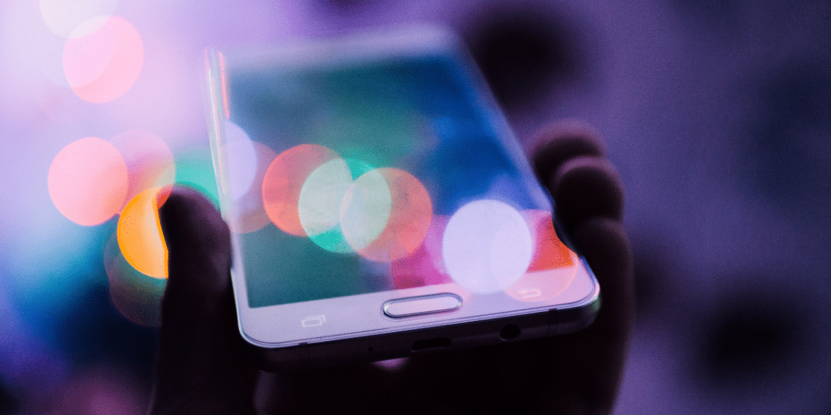 A low-lit image of a hand holding a phone. There are different coloured light leaks reflecting on the phone