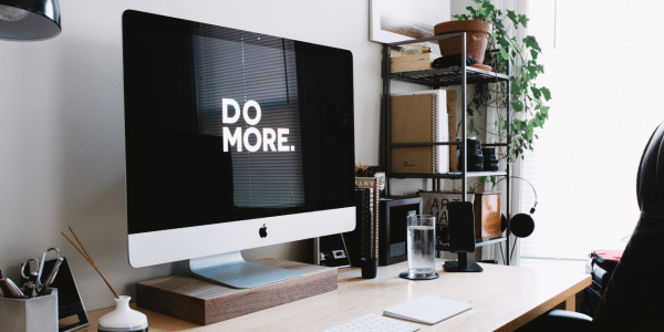 A bright desk space with a large computer screen displaying the words 'DO MORE'